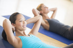 Woman Smiling While Doing Sit-Ups At Gym Royalty Free Stock Photo