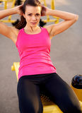 Woman smiling doing situps with hands behind head Royalty Free Stock Photos