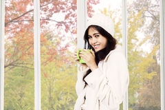 Woman smiling while drinking tea Stock Image