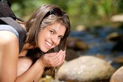 Woman smiling and drinking water with hands from stream Stock Images