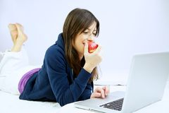 Woman smiling eats apple in front of computer Royalty Free Stock Photo