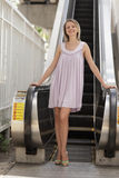 Woman smiling by an escalator Royalty Free Stock Image