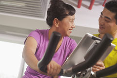 Woman smiling and exercising on the exercise bike with her trainer Stock Photos