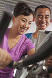 Woman smiling and exercising on the exercise bike with her trainer Stock Images