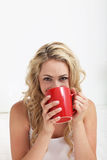 Woman with smiling eyes drinking coffee Stock Images