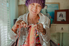 Woman with smiling face happiness emotion knitting working at ho Stock Photos