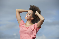 Woman smiling with hand in hair Stock Photo