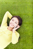 Woman smiling happily on a phone while lying grassland Stock Image