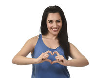Woman smiling happy doing heart shape with her hands and fingers in love and romance Stock Image