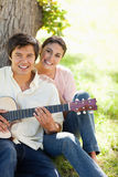 Woman smiling with her friend who is holding a guitar Royalty Free Stock Photos