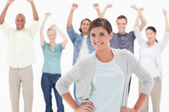 Woman smiling with her hands on her hips. With people behind raising their arms against white background Royalty Free Stock Image