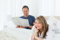 Woman smiling while her husband is reading Royalty Free Stock Photography
