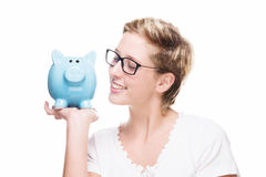 Woman smiling at her piggy bank Stock Photos