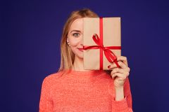 Woman smiling and hiding face behind gift box. Isolated on violet Stock Photo