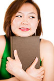Woman smiling holding book happily Royalty Free Stock Image