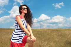 Woman smiling while holding both hands on her knee. Royalty Free Stock Photography