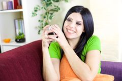 Woman smiling holding cup of coffee at home Stock Image