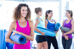 Woman smiling while holding exercise mat Royalty Free Stock Images