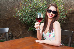 Woman smiling holding glass of wine on terrace. Beautiful woman smiling holding glass of wine outside on terrace table wearing sun glasses with copy text space Stock Photos