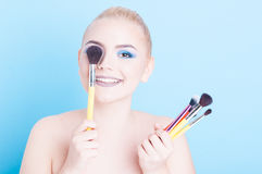 Woman smiling holding many brushes as make-up concept Royalty Free Stock Photos
