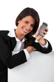 Woman smiling  holding mobile telephone Royalty Free Stock Photo