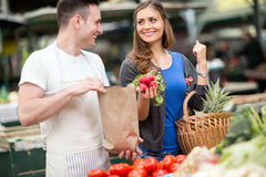 Woman smiling and holding radishes at market Royalty Free Stock Photo