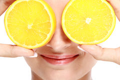 Woman smiling while holding slices of lemon in front of her eyes Stock Photography
