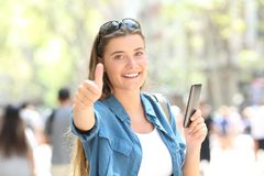 Woman smiling holding a smart phone with thumb up. Happy woman smiling holding a smart phone with thumb up in the street Stock Images