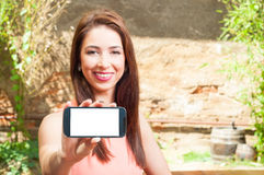 Woman smiling holding smartphone with blank screen Royalty Free Stock Images
