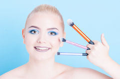 Woman smiling holding three professional make-up brushes Stock Images