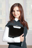 Woman smiling and holds secretary black folder on the chest Royalty Free Stock Photo