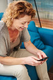 Woman smiling at home writing text on smart phone Royalty Free Stock Photos