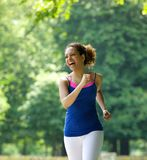 Woman smiling and jogging in the park Stock Photography