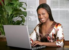Woman smiling at laptop Stock Images