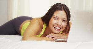 Woman smiling with laptop on bed Royalty Free Stock Images