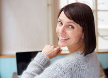 Woman smiling with laptop. Behind portrait woman smiling at home with laptop Royalty Free Stock Photos