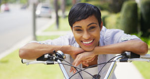 Woman smiling and leaning on bicycle handlebars. African woman smiling and leaning on bicycle handlebars Stock Photos