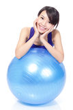 Woman smiling leaning on pilates ball Royalty Free Stock Photos