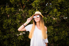 Woman smiling while leaning on wall outdoors ,happy stylish woman in glasses and hat standing at green leaves wall, summer travel Royalty Free Stock Photos