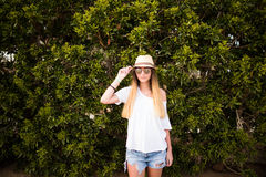Woman smiling while leaning on wall outdoors ,happy stylish woman in glasses and hat standing at green leaves wall, summer travel Stock Images