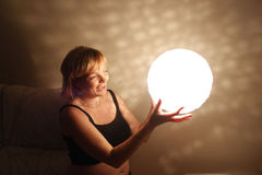 Woman smiling with a light ball. At night Royalty Free Stock Photography