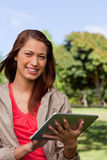 Woman smiling and looking ahead while she uses a tablet in a par Stock Photos