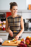 Woman smiling looking into distance while cutting apples Royalty Free Stock Photos
