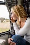 Woman smiling and looking out train window Royalty Free Stock Images
