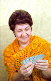 Woman smiling, looking at playing cards. Woman looking at playing cards and smiling Stock Images