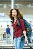 Woman smiling with luggage at airport Royalty Free Stock Photos