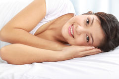 Woman smiling while lying down on bed Stock Photo