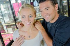Woman smiling while man helping trying necklace Royalty Free Stock Photos