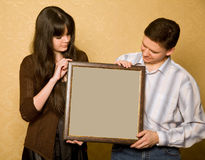 Woman and smiling man with picture in frame Royalty Free Stock Images