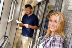 Woman smiling and man reading in train Royalty Free Stock Images